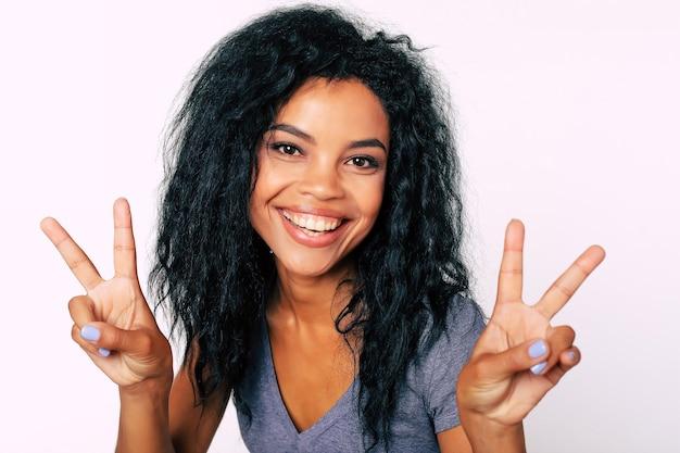 Ritratto integrale di donna etnica africana felicissima con occhi scuri a forma di mandorla e capelli folti guardando la telecamera e mostrando il segno v