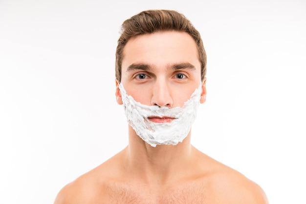Un ritratto integrale di giovane uomo con crema da barba in bagno