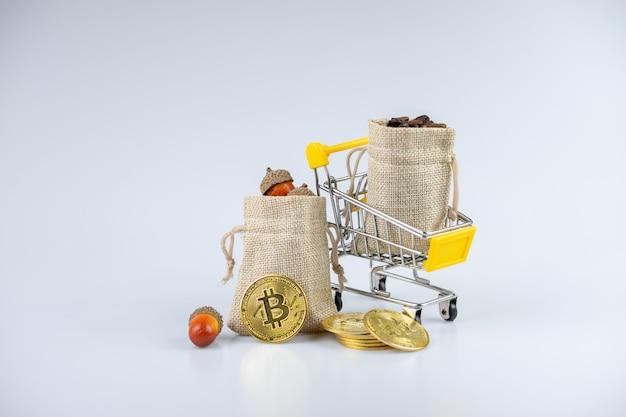 Sacchi pieno pieno di ghiande e chicchi di caffè, su un carrello, accanto a monete d'oro.