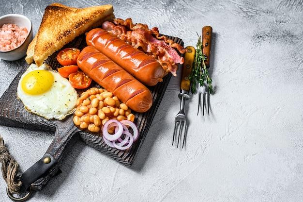 Friggere la colazione all'inglese con uova fritte, salsicce, pancetta, fagioli e toast su un tagliere di legno