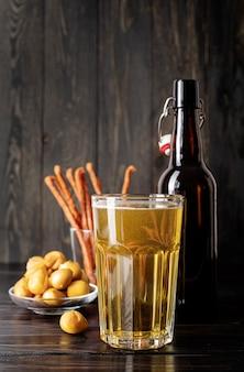 Bicchiere pieno di bottiglia di birra e snack in legno nero sullo sfondo black