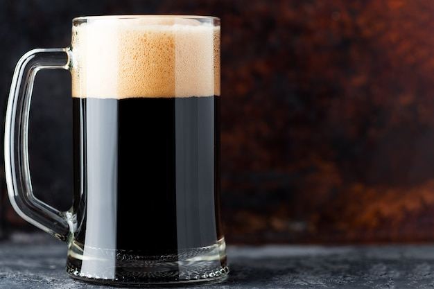 Boccale di vetro pieno di birra scura su una superficie arrugginita