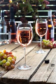 Bicchieri pieni di vino rosato, attività ricreative all'aperto, tavolo in legno con bicchieri di vino, bottiglie di vino e uva