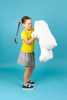 A tutta altezza la ragazza che balla con un orsacchiotto bianco
