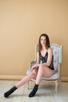 Ritratto a tutta altezza. bella ragazza castana in tuta combo sexy lacci neri seduto su una sedia vintage. lingerie di moda. donna di lusso.