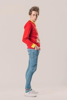 Ritratto a tutta altezza di un giovane ragazzo alla moda.