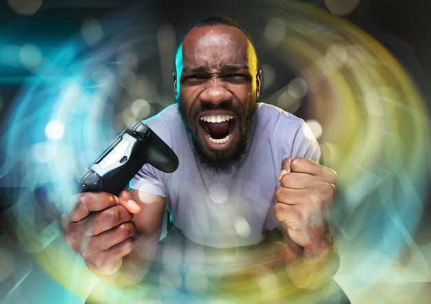 Full immersion nel gameplay giovane che tiene in mano un controller per videogiochi isolato su colorato