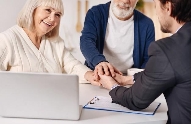 Pieno di gioia. sorridendo felice coppia di anziani seduti a casa e concludendo un accordo con l'agente immobiliare mentre si stringono la mano ed esprimono felicità