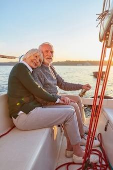 A tutta lunghezza di felice coppia anziana uomo e donna anziani che si tengono per mano abbracciandosi e trascorrendo del tempo