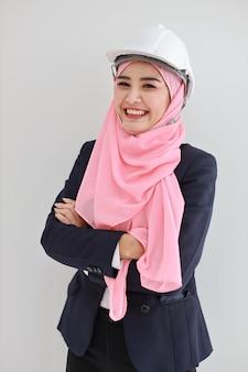 Donna musulmana asiatica adulta intera dell'ingegnere in vestito blu che sta e che ride con sicuro