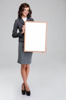 Ritratto a figura intera di una donna d'affari con gli occhiali e un abito grigio che tiene un bordo bianco