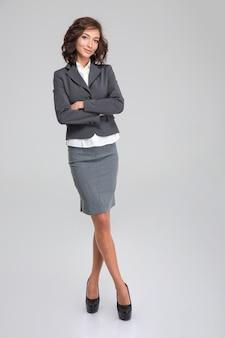 Ritratto a figura intera di donna d'affari su muro bianco