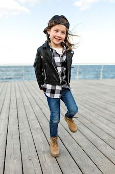 Ritratto a figura intera di piccola ragazza affascinante vestito berretto e giacca di pelle divertendosi e in posa vicino al mare