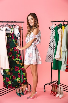 Integrale della donna adorabile in vestito che sta vicino al guardaroba con i vestiti e che sceglie cosa indossare isolato sul rosa
