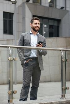 Uomo adulto integrale in vestito grigio che tiene smartphone e guarda avanti, mentre in piedi davanti al moderno edificio per uffici