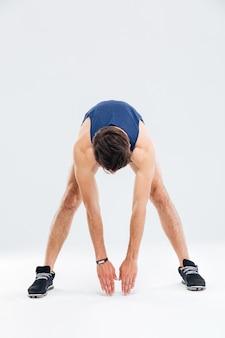 Per tutta la lunghezza del giovane atletico che si allena e fa esercizi di stretching su sfondo bianco