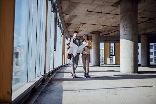 Integrale di attraenti architetti caucasici che camminano nel futuro centro commerciale e parlano di nuove idee per la costruzione. uomo che tiene le cianografie mentre la donna che tiene la documentazione.