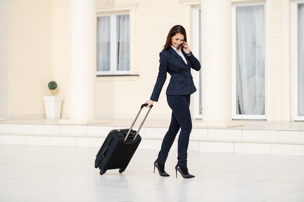 Integrale dei bagagli di trazione casuali astuti vestiti castana sorridenti caucasici attraenti e per mezzo dello smart phone per chiamare taxi. concetto di viaggio d'affari.
