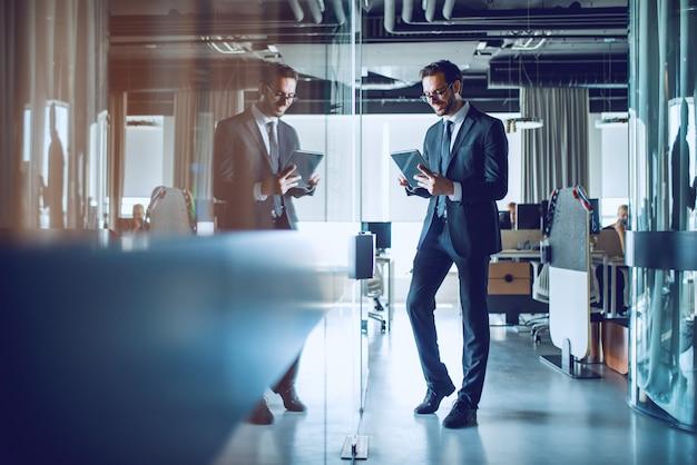 Integrale dell'uomo d'affari caucasico sorridente elegante attraente in vestito e con gli occhiali che stanno davanti al suo ufficio e facendo uso della compressa.