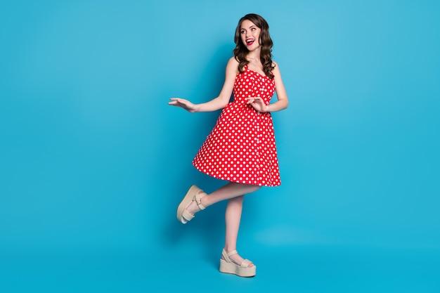Tutta la lunghezza attraente bella signora buon umore flirty alza la gamba ballando
