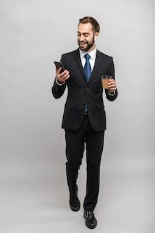 Per tutta la lunghezza di un attraente giovane uomo d'affari sorridente che indossa un abito isolato su un muro grigio, indossa gli auricolari, utilizza il telefono cellulare mentre beve caffè da asporto