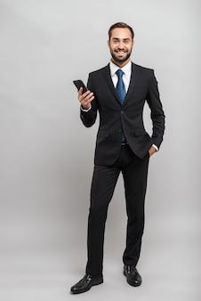 Per tutta la lunghezza di un attraente giovane uomo d'affari sorridente che indossa un abito in piedi isolato su un muro grigio, con in mano un telefono cellulare