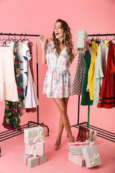 Tutta la lunghezza del vestito da portare della donna attraente in piedi in negozio vicino a stendibiancheria con acquisti isolati in rosa