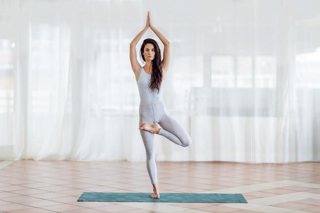 Integrale della donna attraente dello yogi che sta sull'uomo nella posa di yoga del loto mezzo diritto.