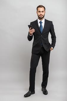 Per tutta la lunghezza di un attraente giovane uomo d'affari che indossa un abito in piedi isolato su un muro grigio, con in mano un telefono cellulare