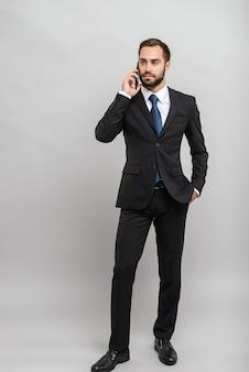 Per tutta la lunghezza di un attraente giovane uomo d'affari che indossa un abito in piedi isolato su un muro grigio, parlando al telefono cellulare