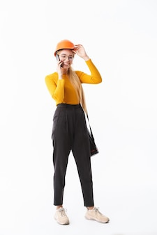 Per tutta la lunghezza di un'attraente giovane donna architetto in piedi isolata su un muro bianco, che trasporta tubo, parla al cellulare