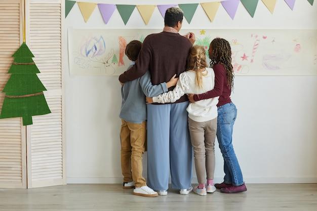Vista posteriore a tutta lunghezza dell'insegnante femminile che disegna sui muri con un gruppo multietnico di bambini mentre si gode la lezione d'arte a natale, copia dello spazio