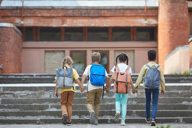 Vista posteriore a tutta lunghezza al gruppo multietnico di bambini che vanno a scuola con zaini e si tengono per mano mentre salgono le scale per un grande edificio, spazio di copia