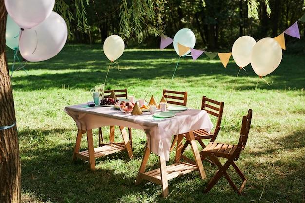 Immagine di sfondo a figura intera di un tavolo da picnic estivo all'aperto decorato con palloncini per feste di comple...