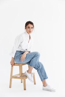 Integrale di una bella giovane donna sensuale con lunghi capelli castani ricci che indossa una camicia bianca seduta su una sedia isolata sopra il muro bianco, in posa