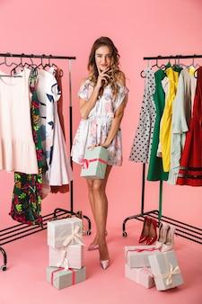 Per tutta la lunghezza del vestito da portare della bella donna che sta nel deposito vicino all'appendiabiti con gli acquisti isolati sul colore rosa