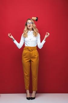 Integrale di una giovane e bella donna bionda in piedi isolato su sfondo rosso, bilanciamento, tenendo la tazza di caffè