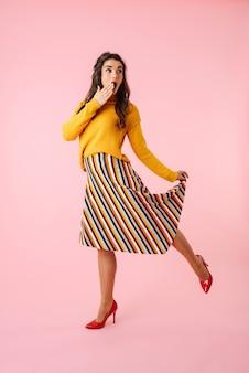 Integrale di una bella giovane donna che indossa abiti colorati isolati su rosa, saltando