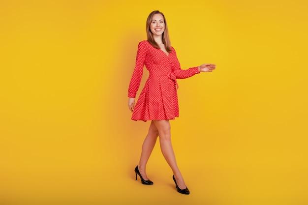 Le dimensioni del corpo di una bella ragazza carina camminano su sfondo giallo con un vestito corto rosso fantasia con i tacchi alti