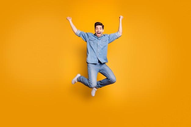 Foto integrale di dimensioni del corpo dell'uomo di gioia eccitato pazzo dai capelli castani che salta su urlando isolato sopra la parete di colore giallo vivido