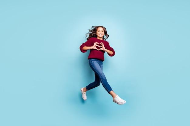 Foto integrale di dimensioni del corpo dell'amica positiva allegra che salta in esecuzione che mostra il segno del cuore che indossa jeans denim maglione bordeaux isolato sfondo blu colore vivido
