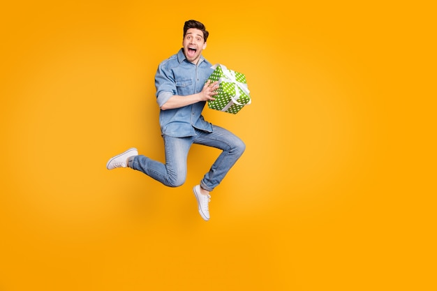 Foto a figura intera di un uomo allegro e felicissimo positivo entusiasta di ricevere il presente consegnato che tiene in esecuzione saltando in uno spazio vuoto isolato muro di colori vivaci
