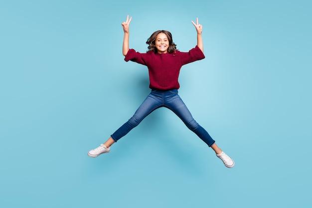 Foto a figura intera del preteen positivo allegro che ti mostra il doppio segno v in maglione lavorato a maglia brugundy sorridente isolato a trentadue denti sfondo blu