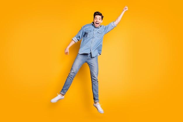 Foto a grandezza naturale di un uomo positivo urlante allegro in calzature bianche che volano via con l'ombrello dal vento che soffia isolato muro di colori vivaci