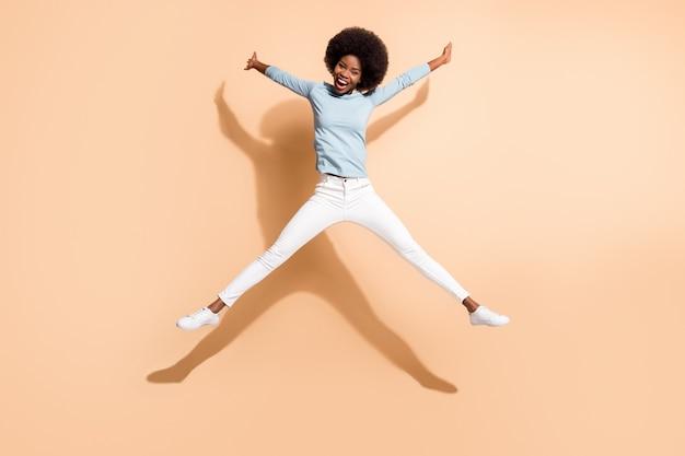 Foto a figura intera di una ragazza riccia e divertente con la pelle scura che salta fingendo una stella isolata su uno sfondo di colore beige