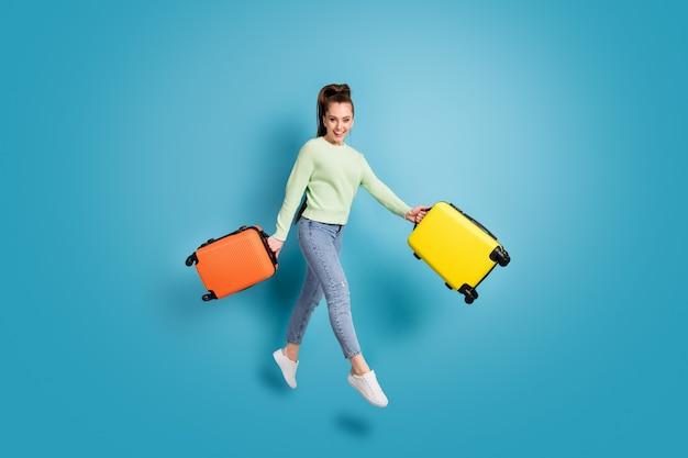 Foto a figura intera di una ragazza allegra che salta tenendo borse colorate prima delle vacanze isolate su uno sfondo di colore blu brillante