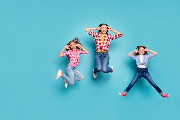 Foto a figura intera della famiglia bianca che salta che ti mostra il segno di v con due dita felicissime che indossano jeans denim mentre sono isolati con sfondo blu