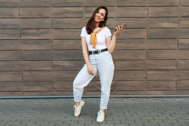 Foto a figura intera di una persona di sesso femminile piuttosto sorridente che indossa abiti casual in piedi nella tenuta della strada e utilizzando il telefono cellulare che guarda l'obbiettivo.