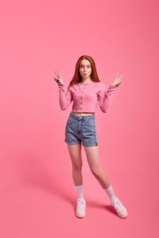 Foto a figura intera di una donna dai capelli rossi in posa che mostra vsign isolato su sfondo di colore rosa vivido...