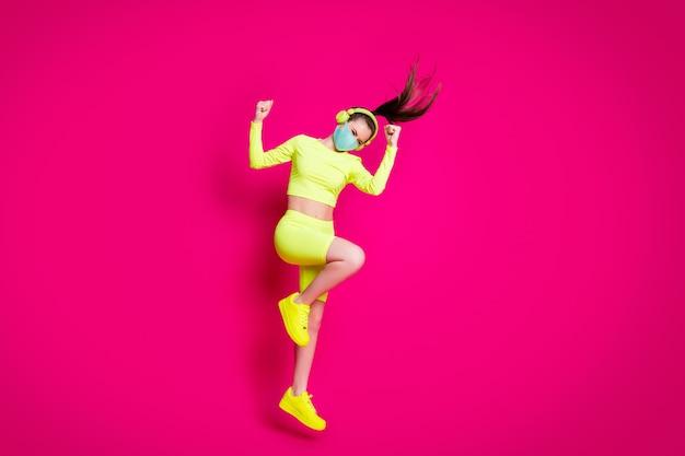 Foto a figura intera di una sportiva che salta dimostrando potenza indossando cuffie con maschera isolate su uno sfondo di colore fucsia vivido